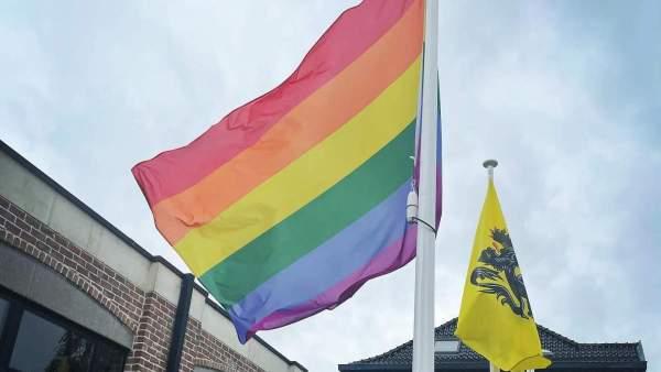Een regenboogvlag aan een vlaggenstok die lichtjes wappert in de wind, naast drie andere vlaggenstokken meer op de achtergrond met de Vlaamse vlag en de vlaggen daarachter zijn moeilijk zichtbaar. De vlaggen staan aan het gemeentehuis van Kortenaken.