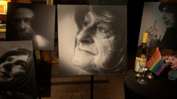 Enkele zwart-wit foto's van transgender personen op staanders in café Rocco, belicht door enkele spots. In het midden van het beeld is een zwart-wit close-up van Ghislaine Bonetto, een vrouw met lichtgekleurde haren die naar links kijkt en lacht. Rechts van de foto van Ghislaine staat een tafel met zwart tafelkleed waar een leeg wijnglas, fles alcohol en een regenboogvlaggetje.