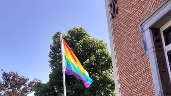 Een regenboogvlag aan een stok langs het gemeentehuis van Dilbeek