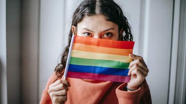 Een persoon houdt een regenboogvlag voor hun gezicht, enkel de ogen zijn zichtbaar.
