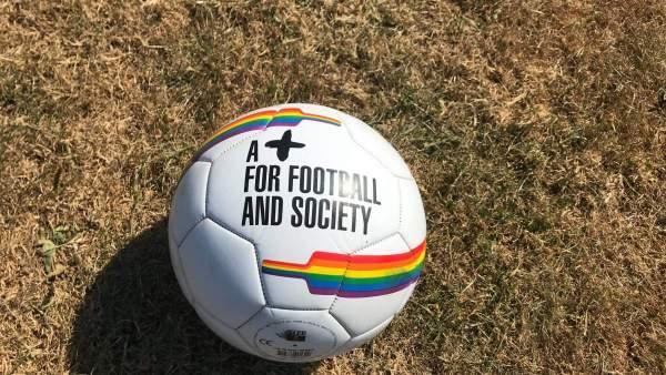 Een witte voetbal op het gras, er staan regenbogen op en in zwarte letters 'A + for football and society'