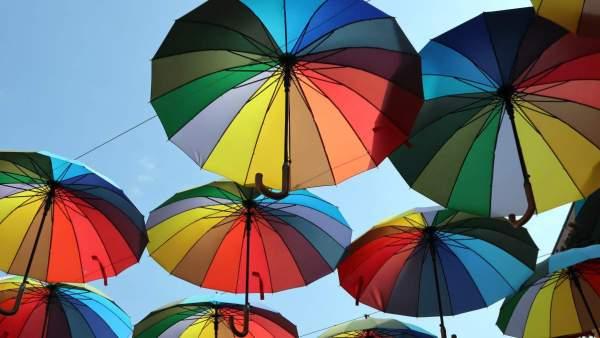 Enkele regenboogparaplu's die in de blauwe lucht lijken te zweven