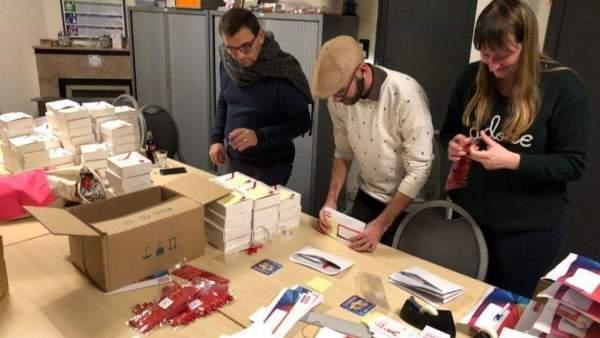 Een foto van drie vrijwilligers van de werkgroep Take Care, staan langs elkaar aan een tafel. De tafel ligt vol met brochures, dozen, lintjes, enveloppes, en dergelijke. De drie personen zijn aan het werk.