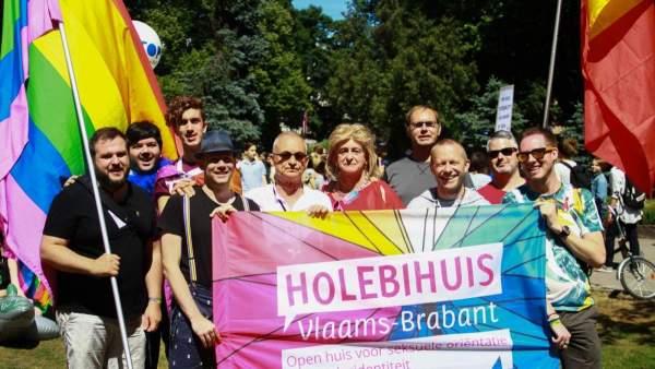 De groep vrijwilligers van het Holebihuis in Riga tijdens de Pride-optocht. Ze dragen regenboogvlaggen, de Belgische vlag en een vlag van het Holebihuis en kijken naar de camera.
