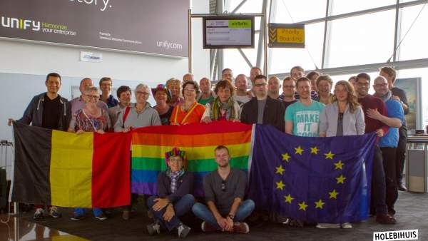 Een groepsfoto van de vrijwilligers van het Holebihuis in een vliegveld, ze houden omhoog een Belgische vlag, regenboogvlag en Europese vlag